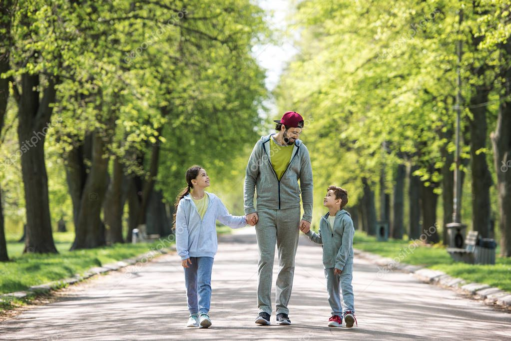 smiling father holding hands of son and daughter and walking in park