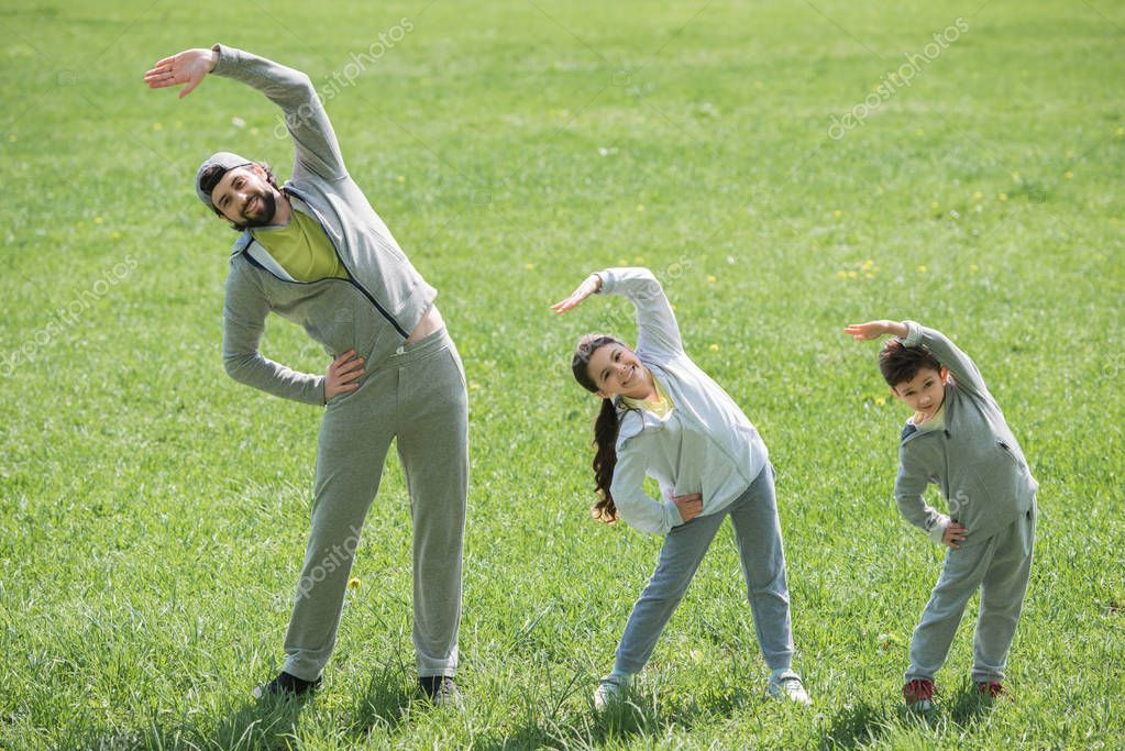 father with daughter and son doing physical exercise on grass