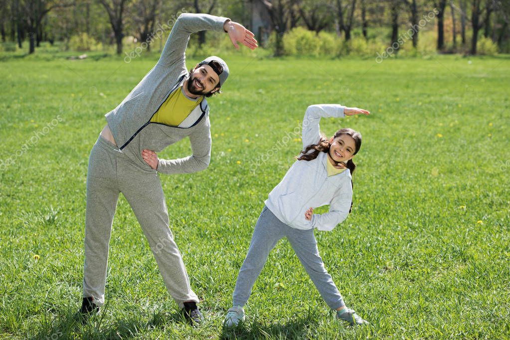 daughter and father doing physical exercise on grass