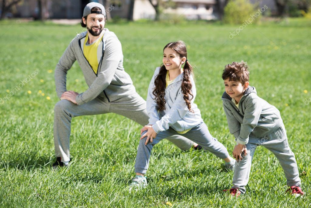 father with daughter and son doing physical exercise on grassy meadow in park