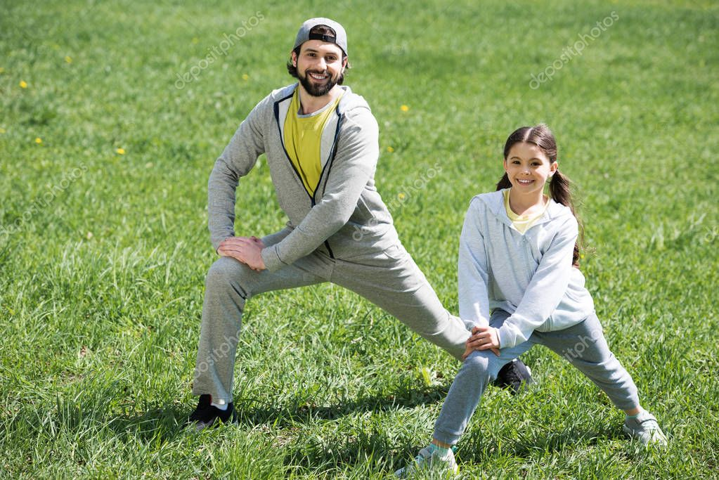father and daughter doing physical exercise on meadow in park