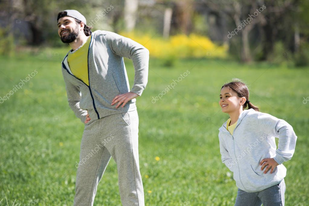happy father and daughter doing physical exercise in park