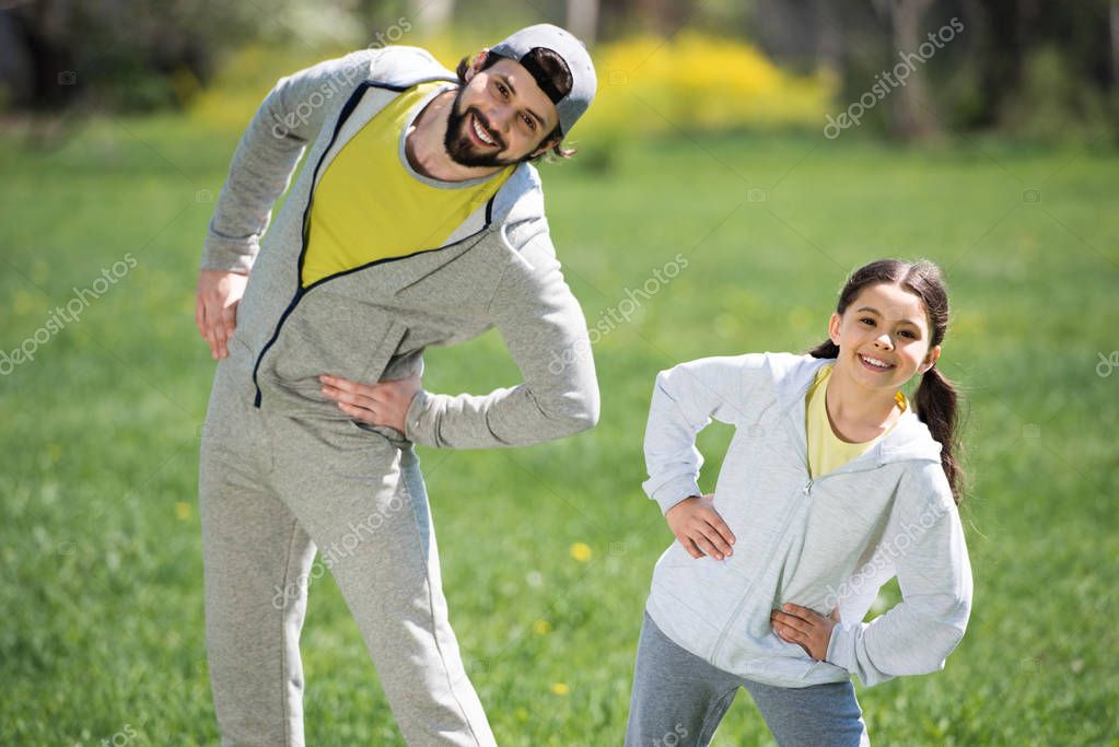 smiling father and daughter doing physical exercise in park