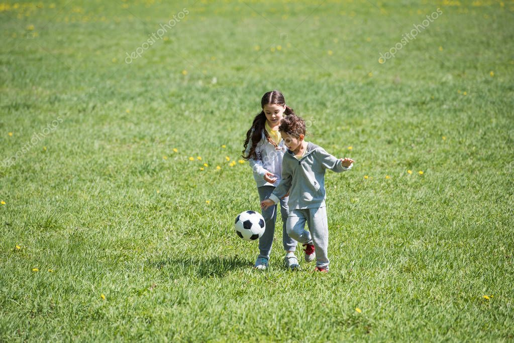little children playing football on grassy meadow in park