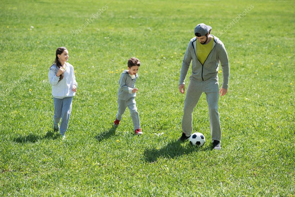 children playing soccer with father in park