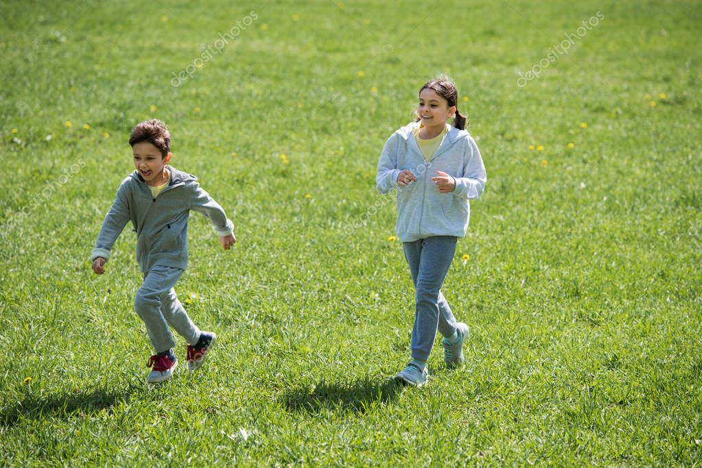 sister and brother running on meadow in park