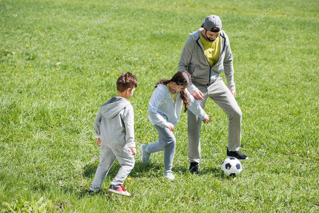 smiling father playing football with daughter and son in park