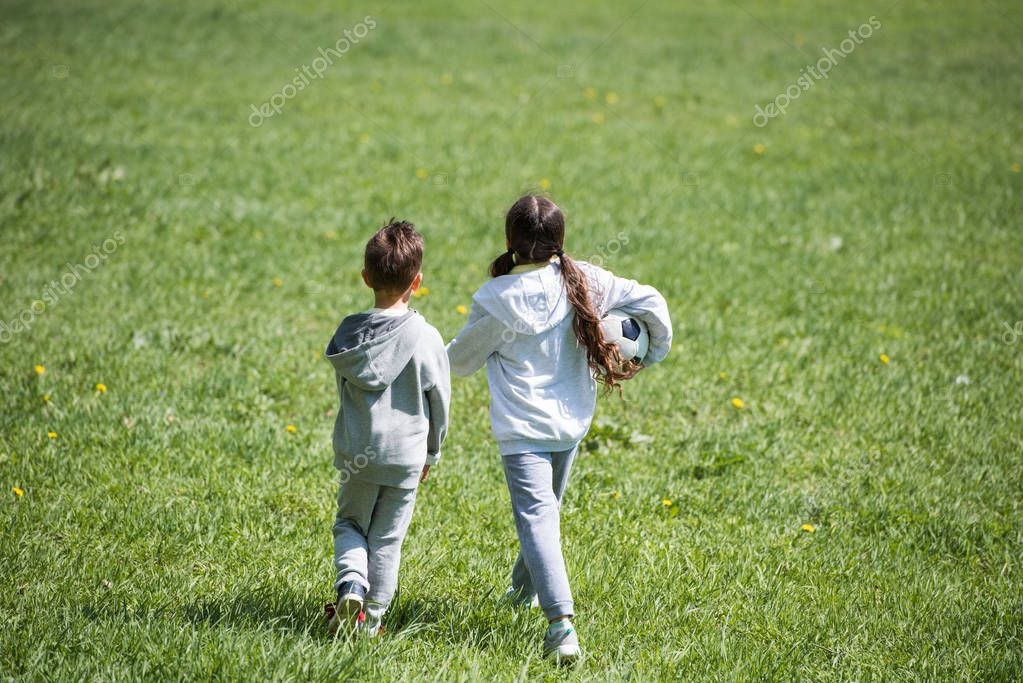 rear view of sister and brother walking with ball on grass