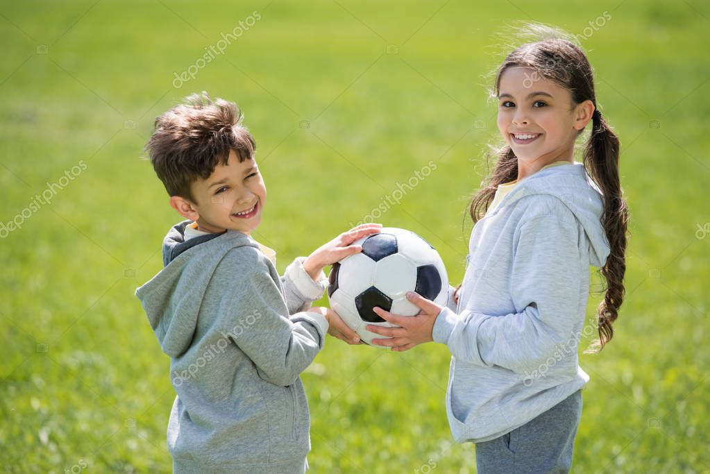 smiling brother and sister holding ball on meadow