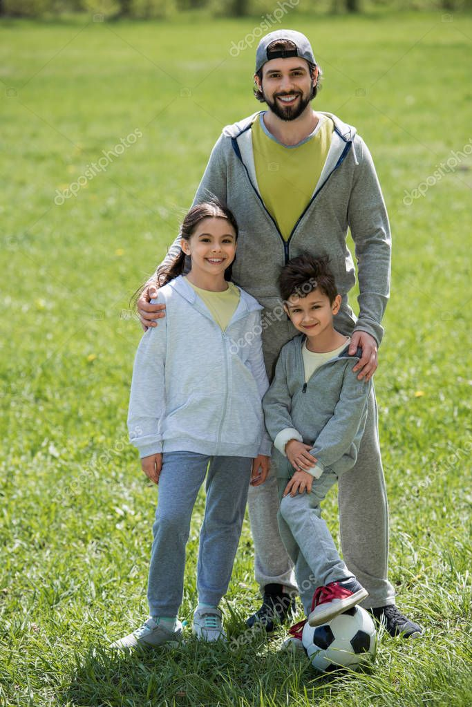 smiling father holding daughter and son with soccer ball in park