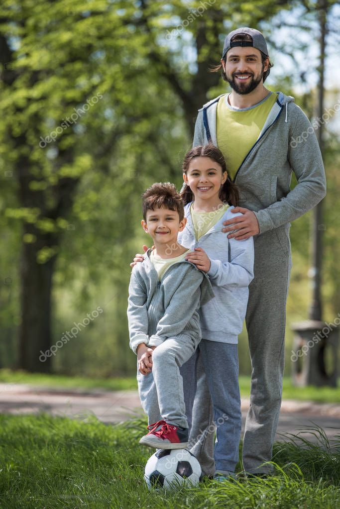 sportive family with soccer ball in park