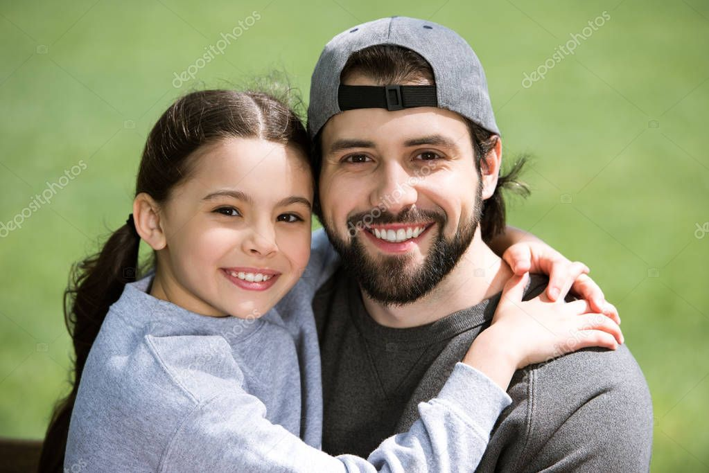 smiling little daughter hugging father