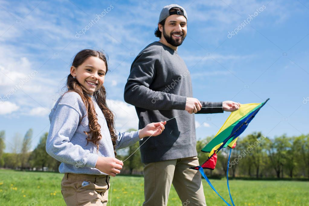 daughter with father holding kite on meadow in park