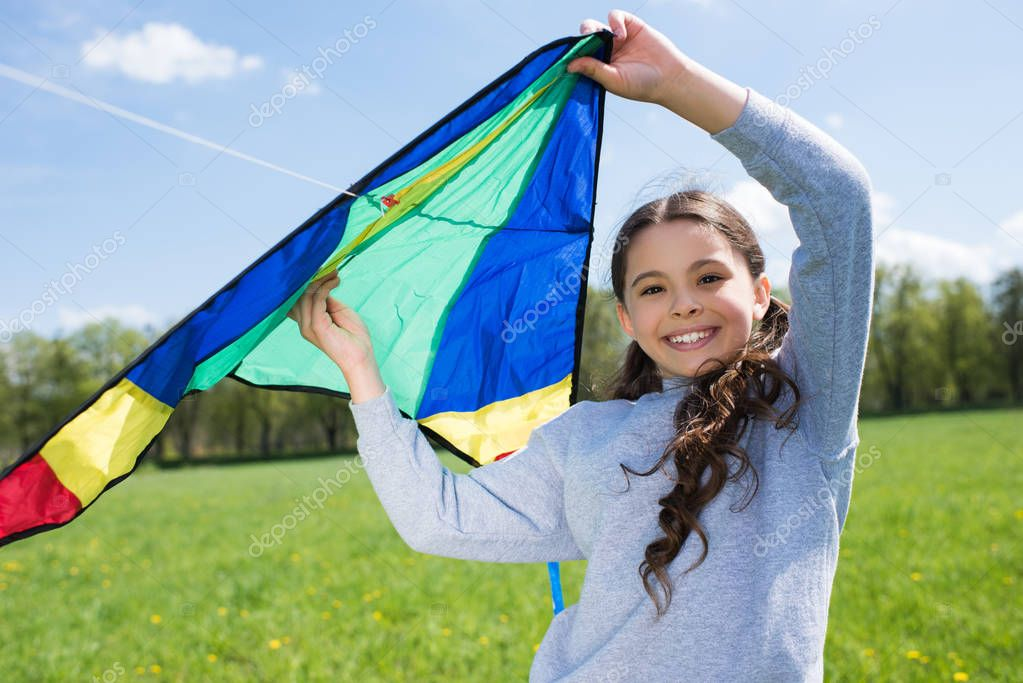 happy little child holding kite on meadow in park