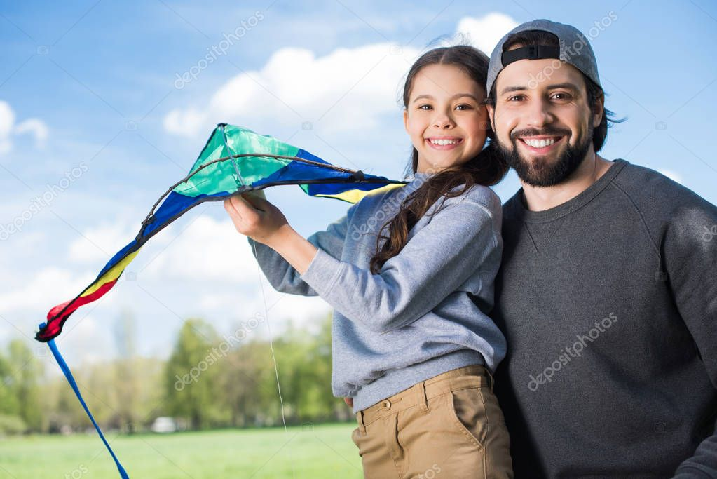 smiling father and daughter holding kite in park