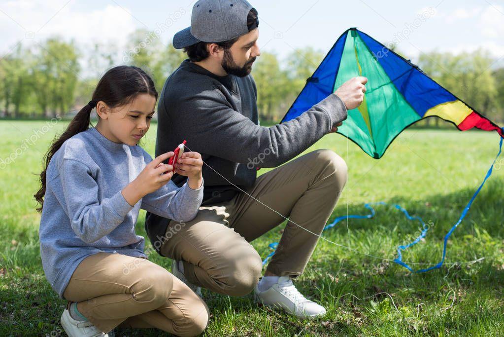 father and daughter sitting with kite on meadow in park