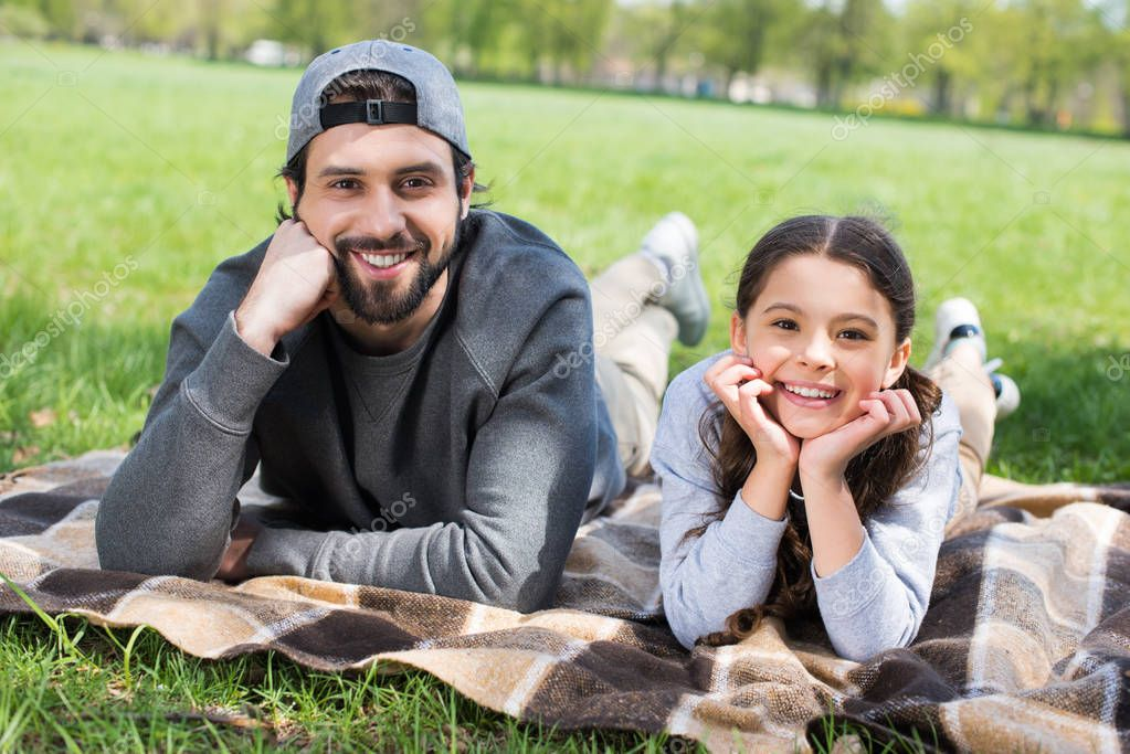 smiling daughter and father laying on plaid in park