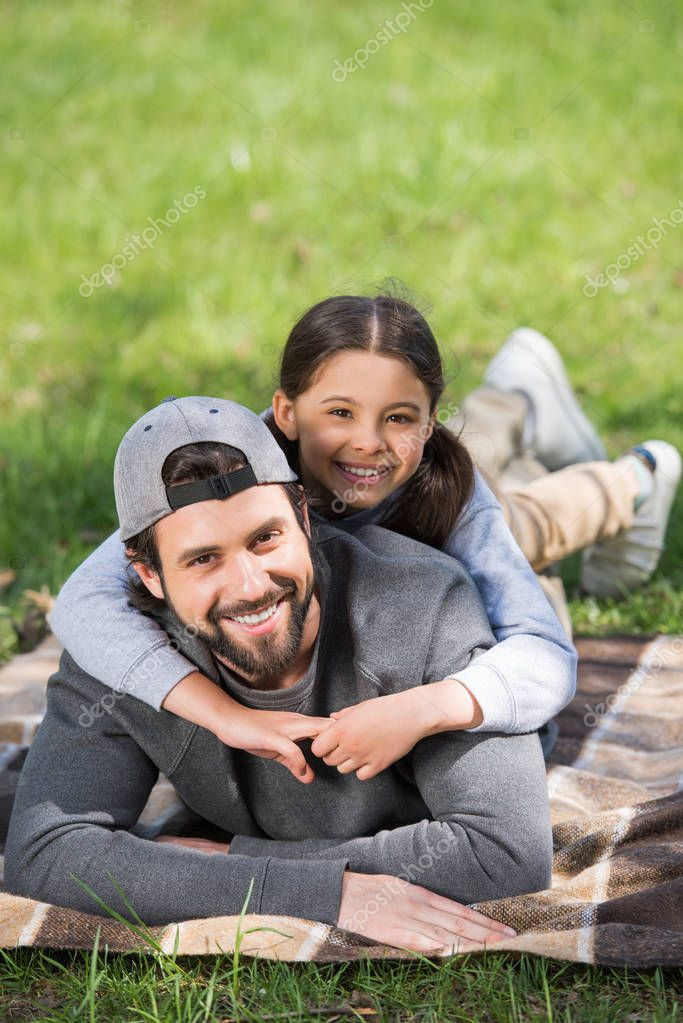 smiling daughter laying on father back in park
