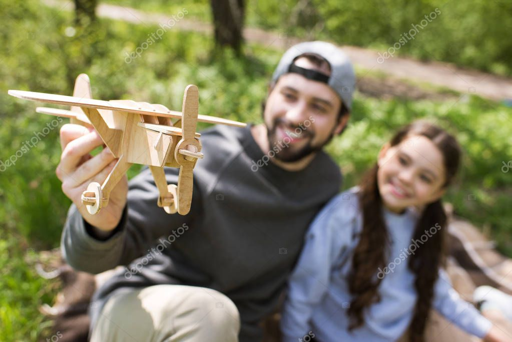 father and daughter playing with wooden toy plane in park