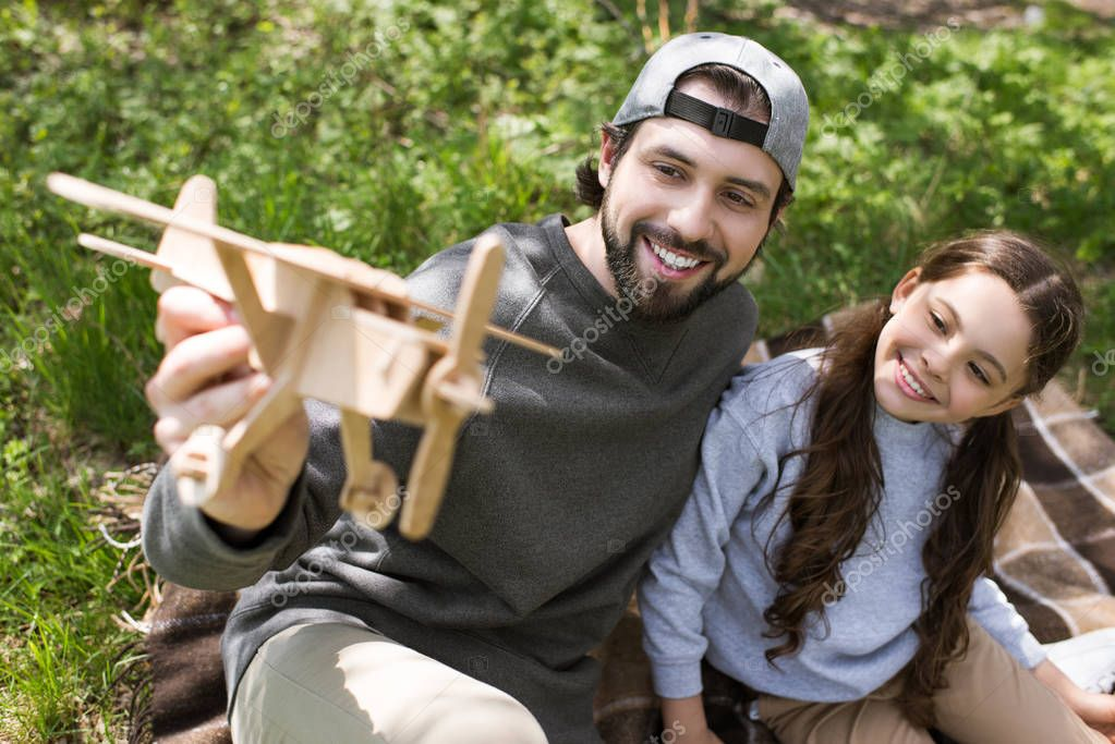 smiling father and daughter playing with wooden toy plane on plaid in park