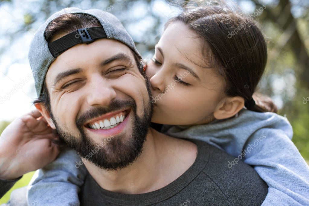 daughter kissing cheek of smiling father