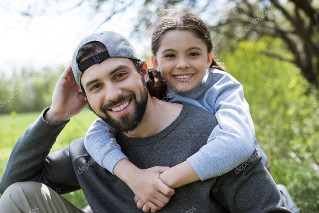 little child embracing smiling father in park