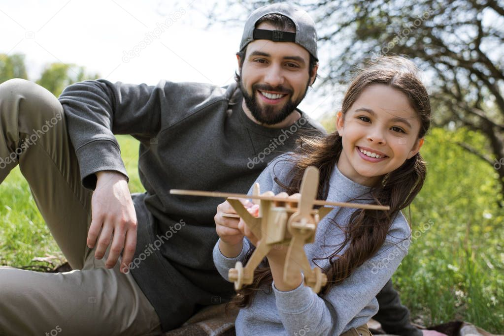 smiling daughter and father playing with wooden toy airplane in park