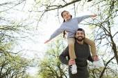 Fotografie low angle view of daughter sitting on father shoulders in park