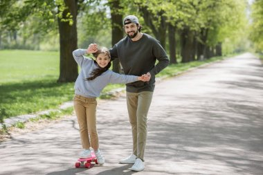 smiling father helping daughter to ride on skateboard in park