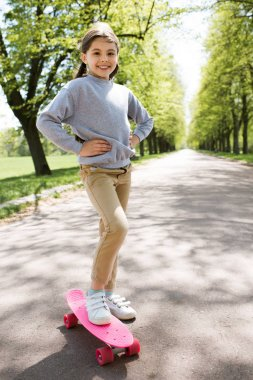 smiling child standing with skateboard on path in park