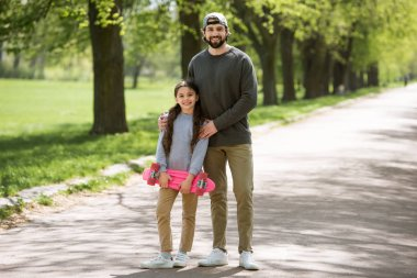 smiling father and daughter holding skateboard in park