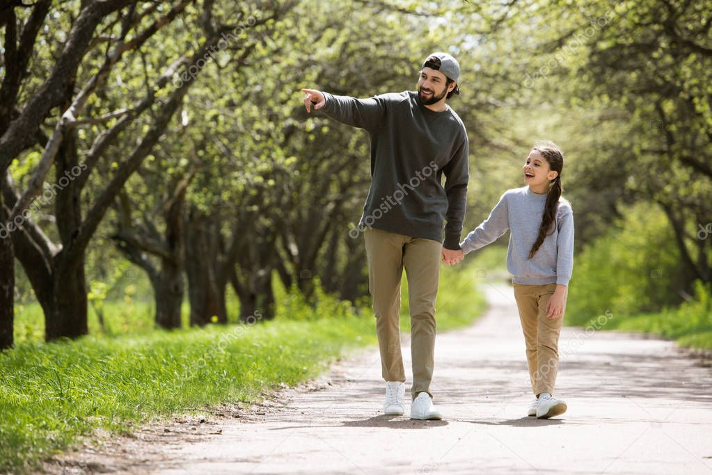 father pointing by finger to daughter in park