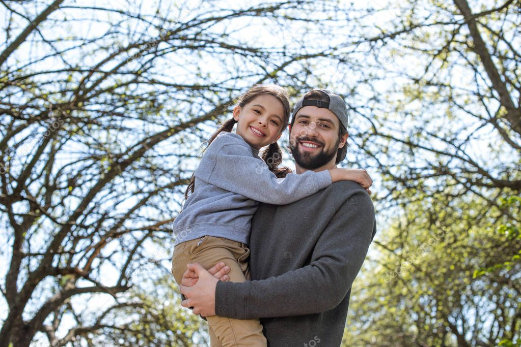low angle view of smiling father holding daughter in park