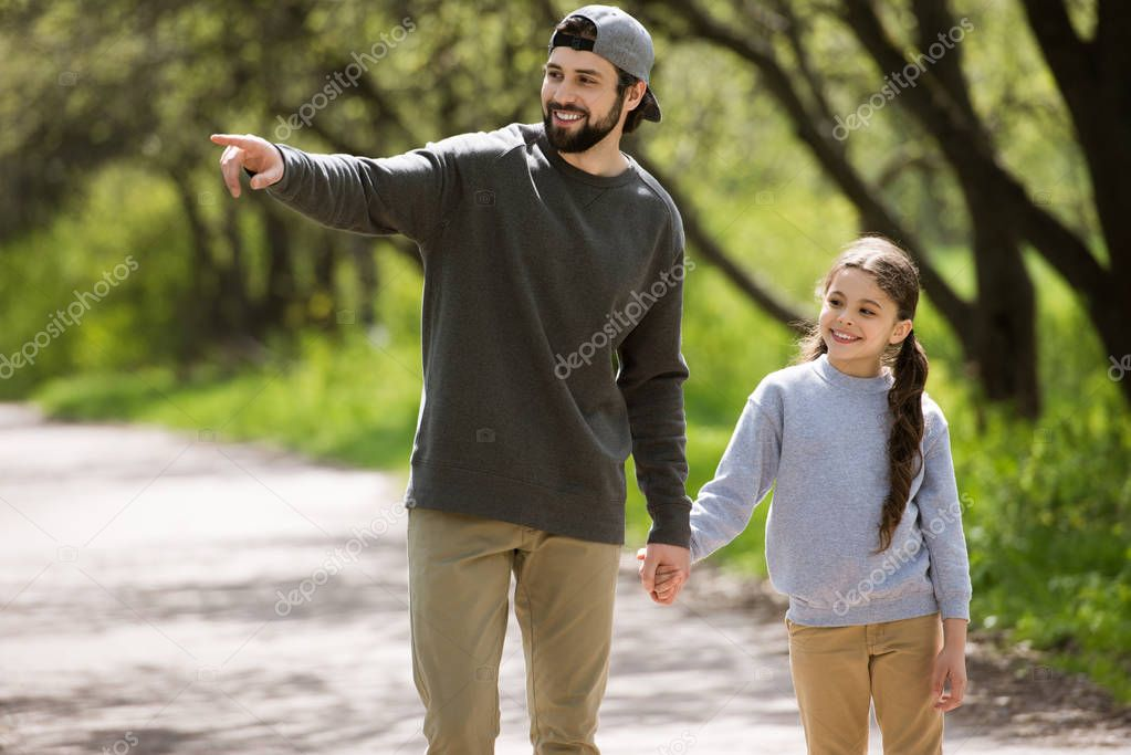 smiling father pointing by finger to daughter in park