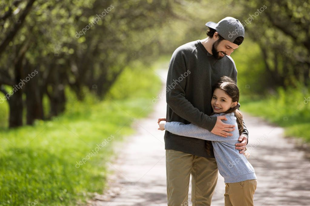 father embracing daughter on path in park