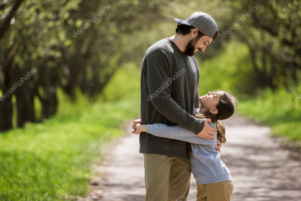 side view of smiling daughter hugging father in park