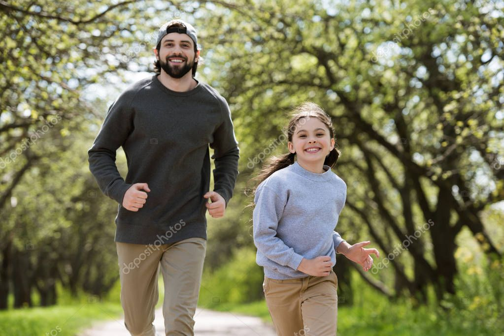 smiling father and daughter running in park