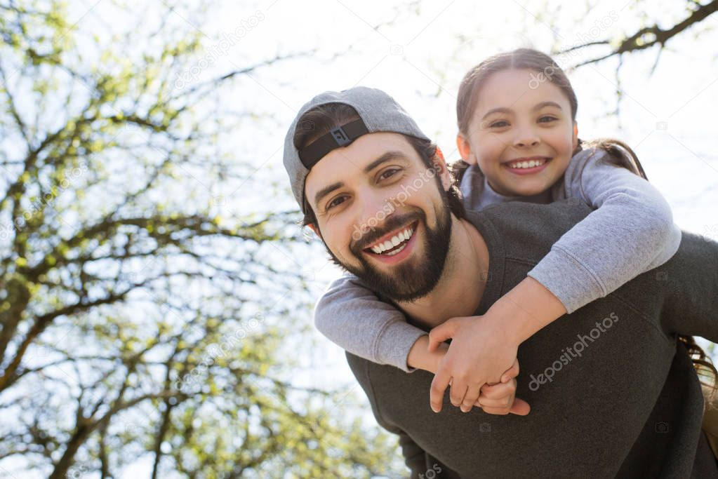 portrait of smiling daughter on father back in park