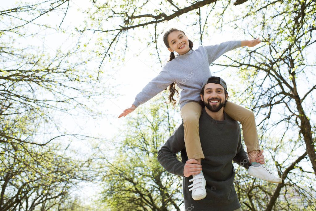 low angle view of daughter sitting on father shoulders in park