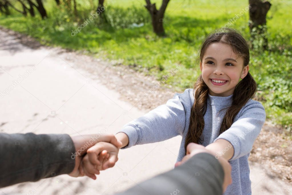cropped image of man holding smiling daughter hands in park