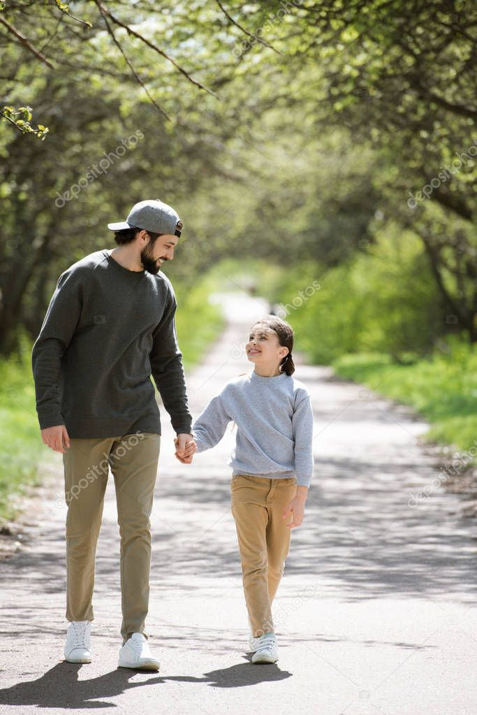 smiling father and daughter walking and holding hands in park