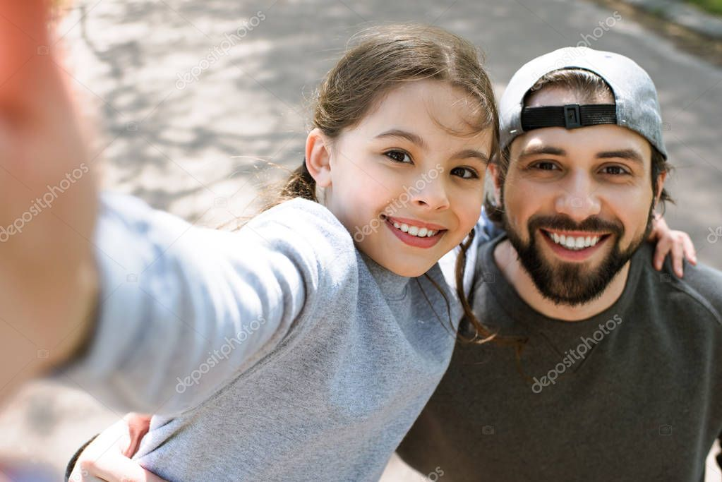 daughter taking selfie smiling father in park