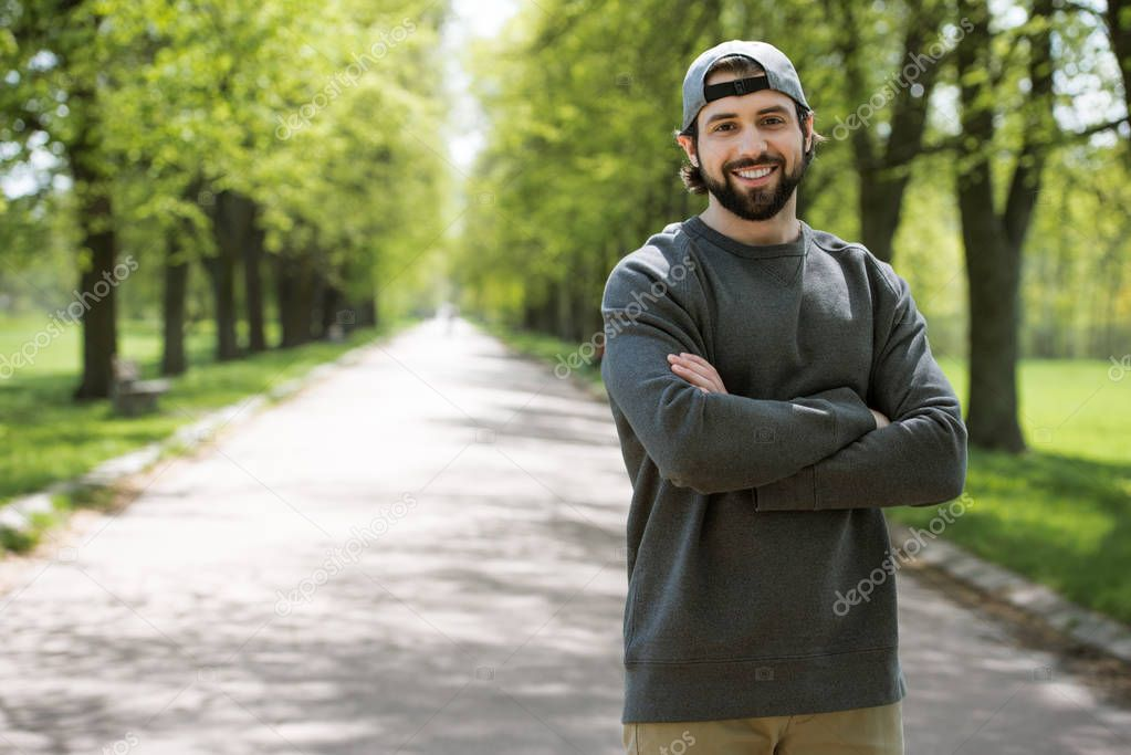 smiling man standing with crossed hands on path in park