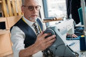 Fotografie handsome tailor sewing cloth with sewing machine at sewing workshop