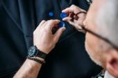 Fotografia immagine potata di sarto di capelli grigi scegliendo i pulsanti al laboratorio di cucito