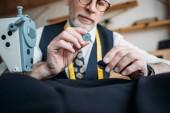 Fotografia immagine potata di attraente su misura scegliendo i pulsanti al laboratorio di cucito