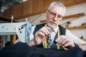 Fotografie handsome tailor holding buttons at sewing workshop
