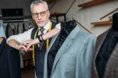 Fotografie stylish mature tailor with measuring tape leaning on mannequin with jacket at sewing workshop