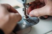 Fotografia ritagliata colpo di sarto lavora con macchina da cucire