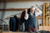 Fotografia sarto maturo bello mettere giacca sulle spalle al laboratorio di cucito